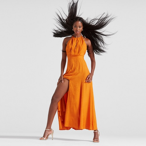A woman wearing a bold gold/orange long dress with a long split, and a high neck. Her hair is blow around by wind.