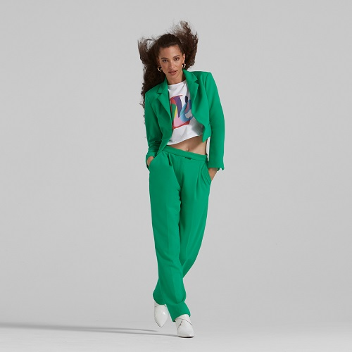 A woman wearing a bright green suit with a white and coloured tshirt under, her hair is blow by the wind.