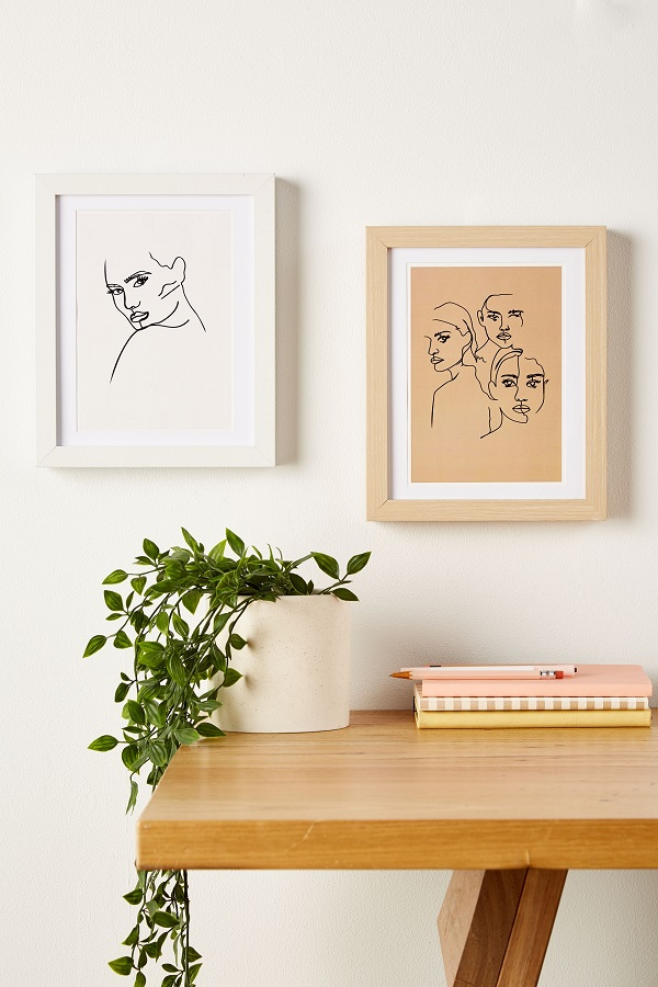 Two figurative art works on a wall behind a shelf with a palnt and books on.