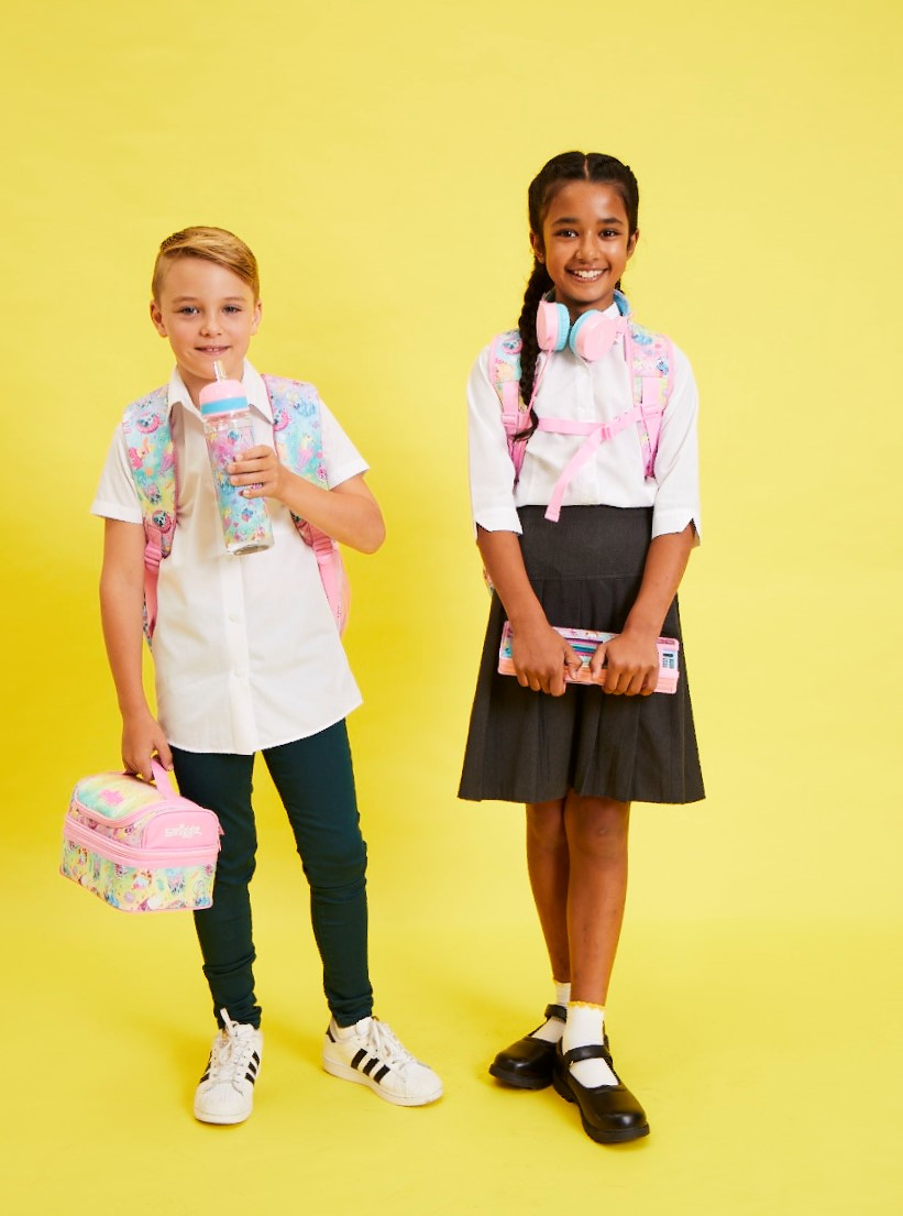 A boy and girl wearing school uniform and colourful smiggle backpacks and lunch boxes.