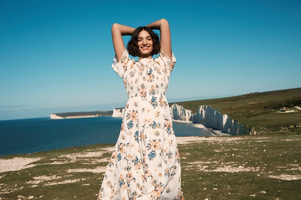 A woman wearing a long floral summer dress, she is standing on cliff tops.