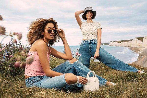 Two women wearing new loo jeans and tshirts, they are standing on a cliff top overlooking a beach.
