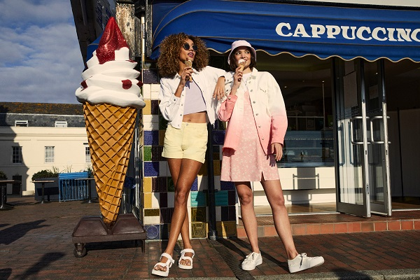 Two women stoof outside an ice cream shop, they are eating ice cream cones. They wear light coloured denim jackets with other clothes underneath.
