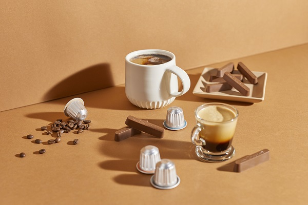 Two different cups of coffee, one in a clear glass and one in a white cup There are coffee pods and chocolates around.