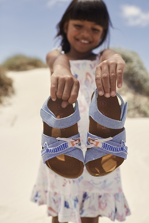 A girl holding blue sandals with mermaids on.
