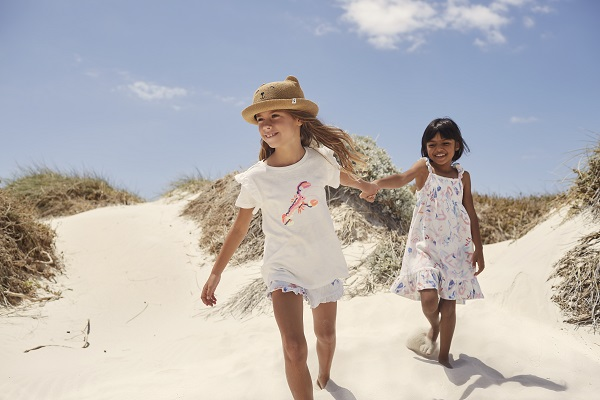 Two girls on a beach wearing joules clothing.