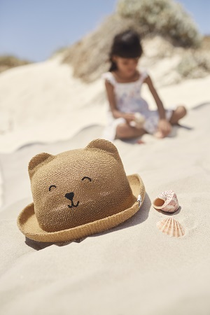 A childs sun hat with a teddy bear face on it.