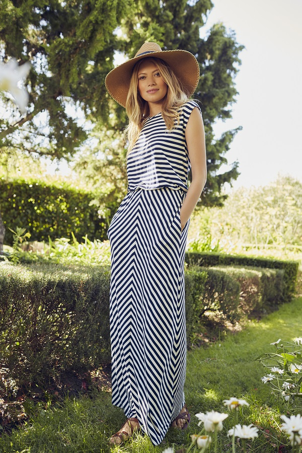 A woman wearing a sun hat and a long striped black and white dress.