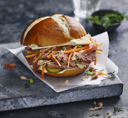 A bread roll with vegan salt beef filling and vegetables.