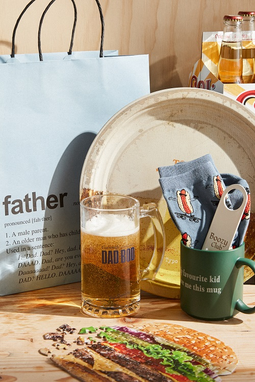 A table with fathers day gifts; a beer stein, a mug, socks with hotdogs on, a burger shaped jigsaw.