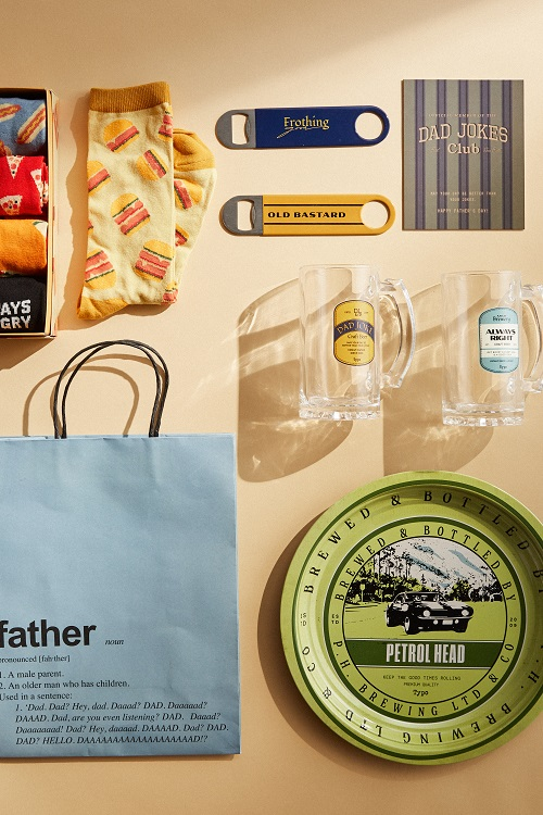 A variety of father's day gifts; socks with burgers on, bottle openers, a beer stein.