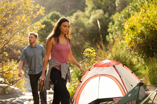 A woman and a man outdoors with a tent. The woman wear a pink vest, black trousers and grey jumper tied round her waist and he wears a grey tshirt and black trousers.