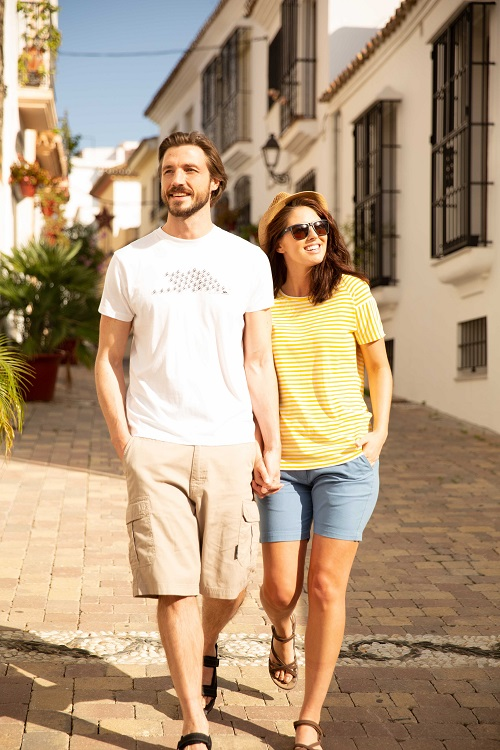 A couple walk down a street holding hands. He wears a white tshirt and beige shorts and she wears a yellow striped shirt and blue shorts.