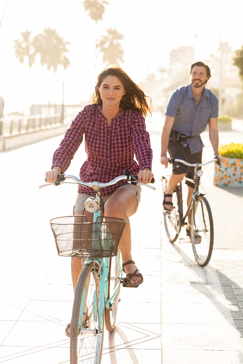 A woman and man on bikes, she wears checked shirt and he wears a blue shirt.