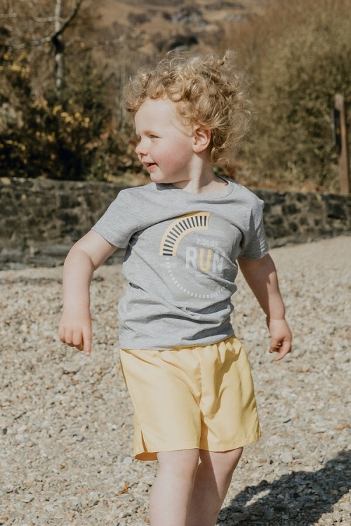 A young boy on a beach, he wears a grey graphic tee and yellow shorts.