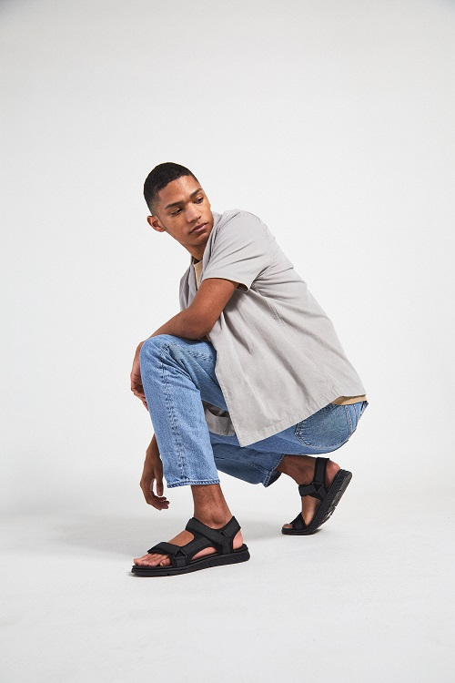 A man wearing black sandals. He is squatting.