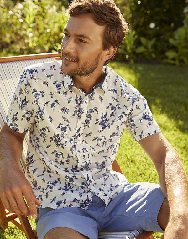 A man sitting on a deck chair, he is wearing a white and blue floral shirt.