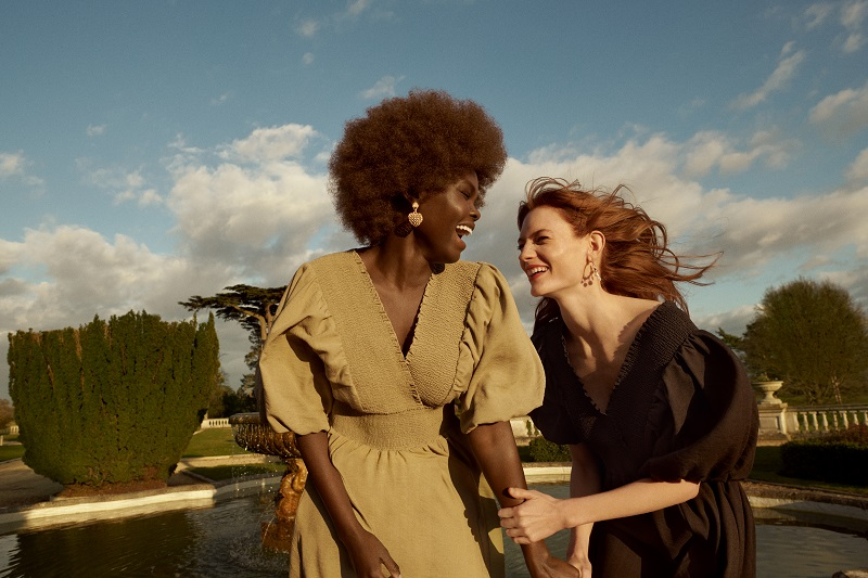 Two women stand and laugh together, they are both wearing brown long sleeved dresses from River Island.