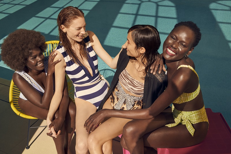 Four women sat on the edge of a pool laughing together, they wear different types of swimming costumes.