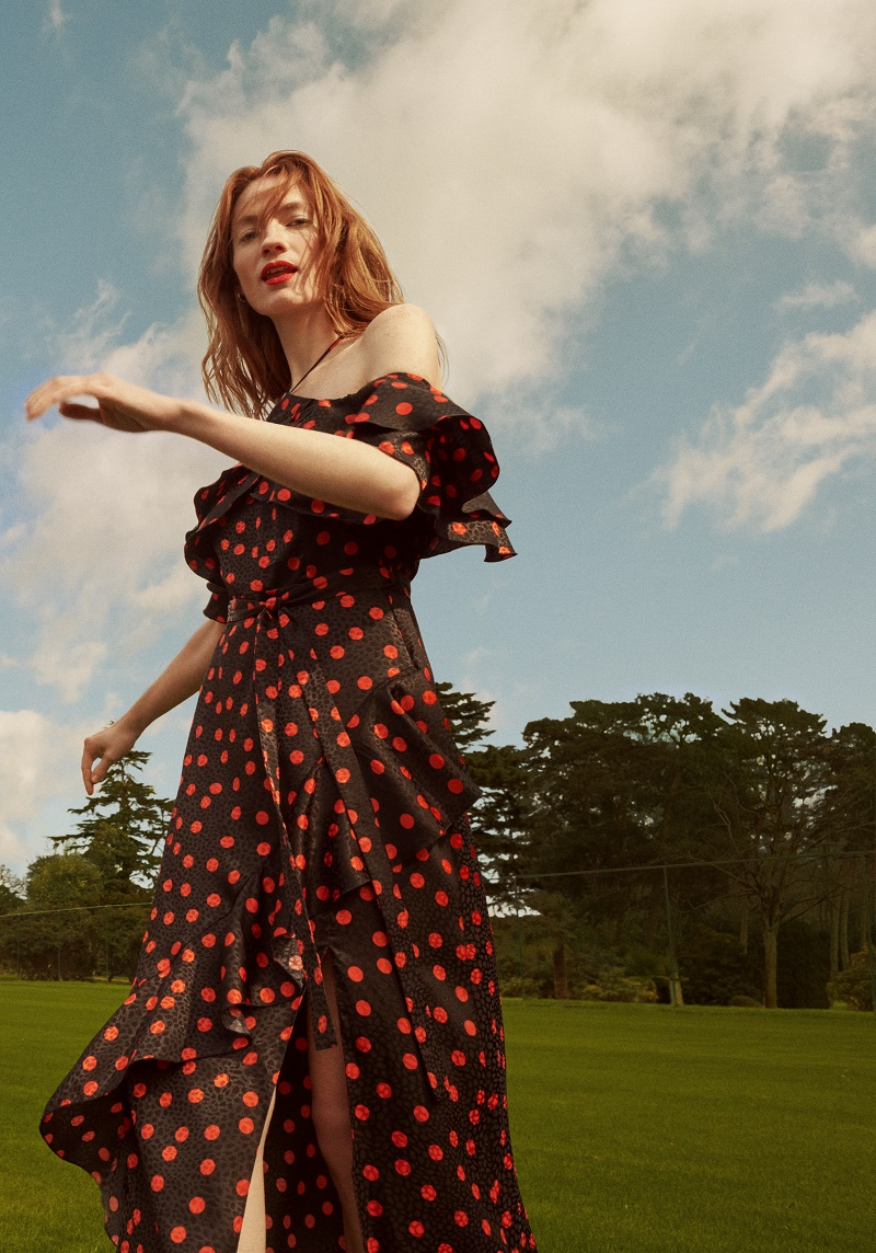 A woman wearing an off should black dress which has large red polka dots on.