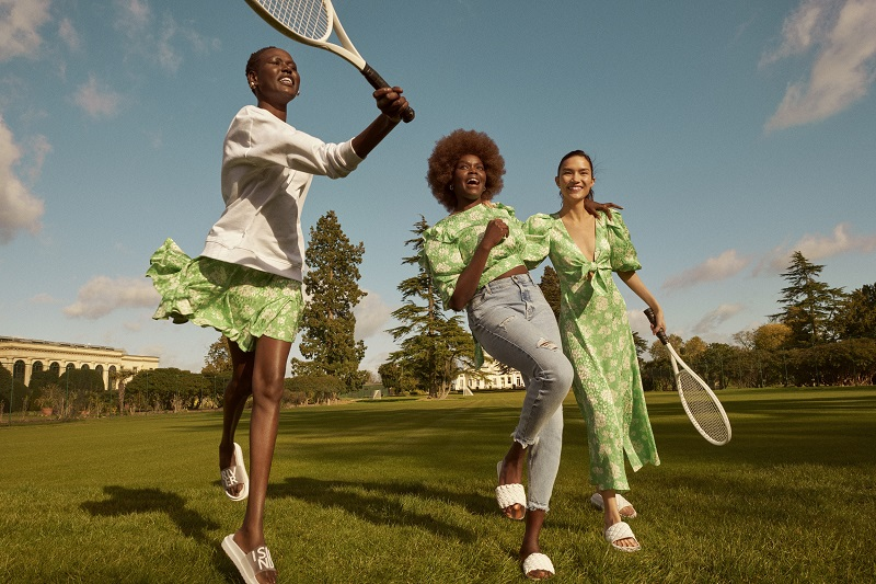 Three women wearing green River Island clothing they have tennis raquets and are jumping up.