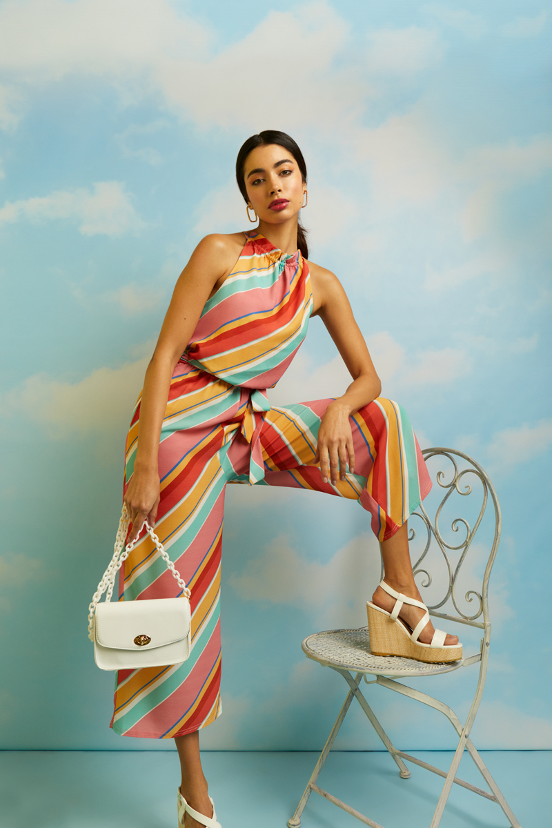 A woman wearing a colourful diagonal striped halterneck jumpsuit or two piece from Quiz.