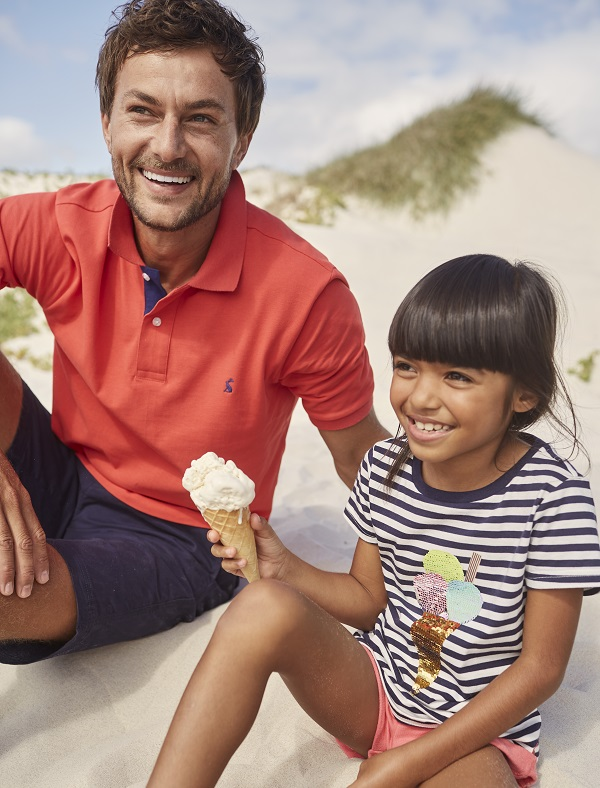 A man and a young girl sit on a beach and eat ice cream. They are wearing Joules clothing.