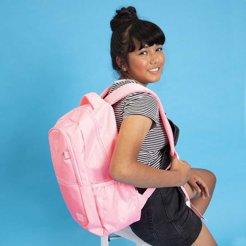 A young girl wearing a pink backpack.