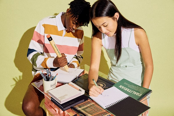 Two people using notepads and pencils at a desk. One of the pencils is oversized.