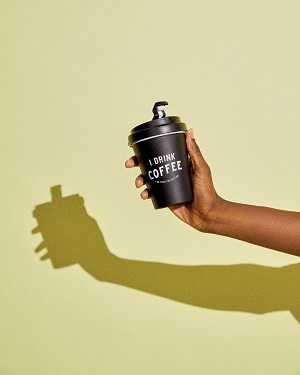 A hand holding a travel coffee cup which says 'I drink coffee' on it.