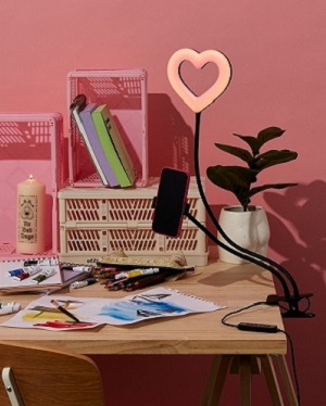 A desk with typo products including a pink heart shape light.
