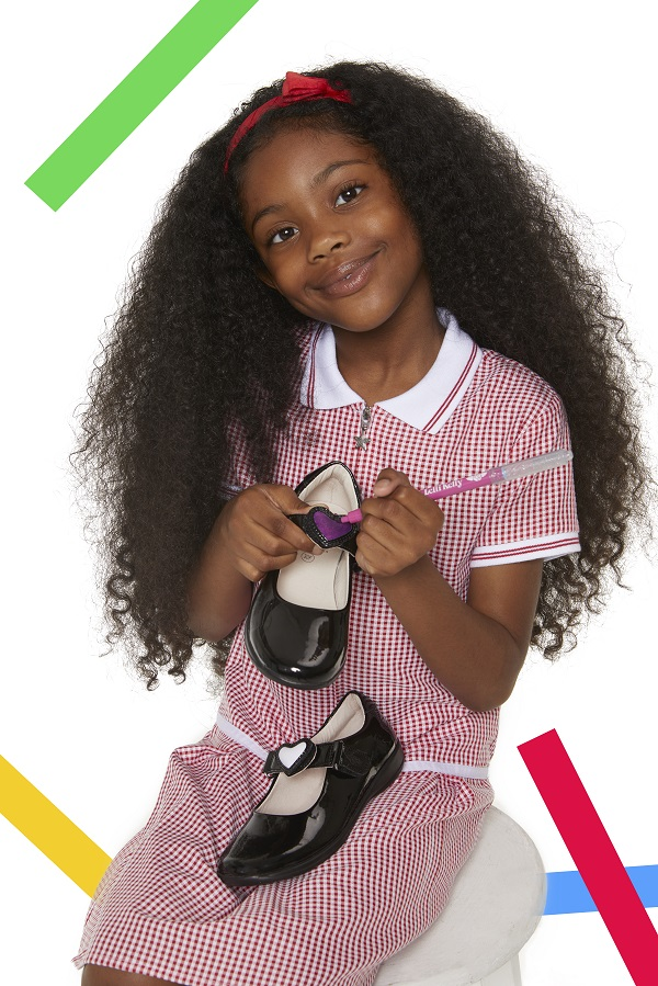 A girl in a school dress holding Schuh school shoes and a pen.