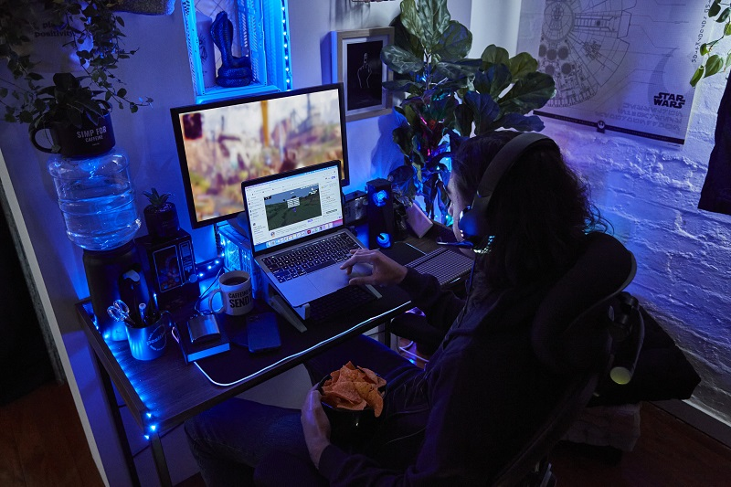 A person sat in front of a computer screen and wearing headphones.