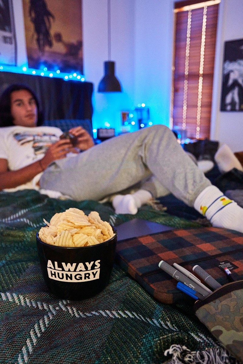 A young person laying on a bed with a bowl of crisps in front of them.