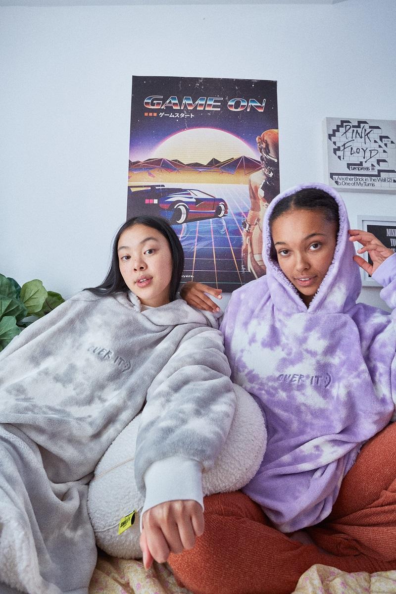 Two young people wearing fleece hooded blankets.