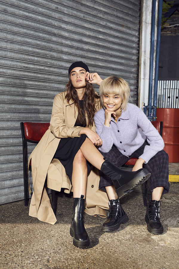 two people sat on chairs wearing chunky black boots from Schuh.