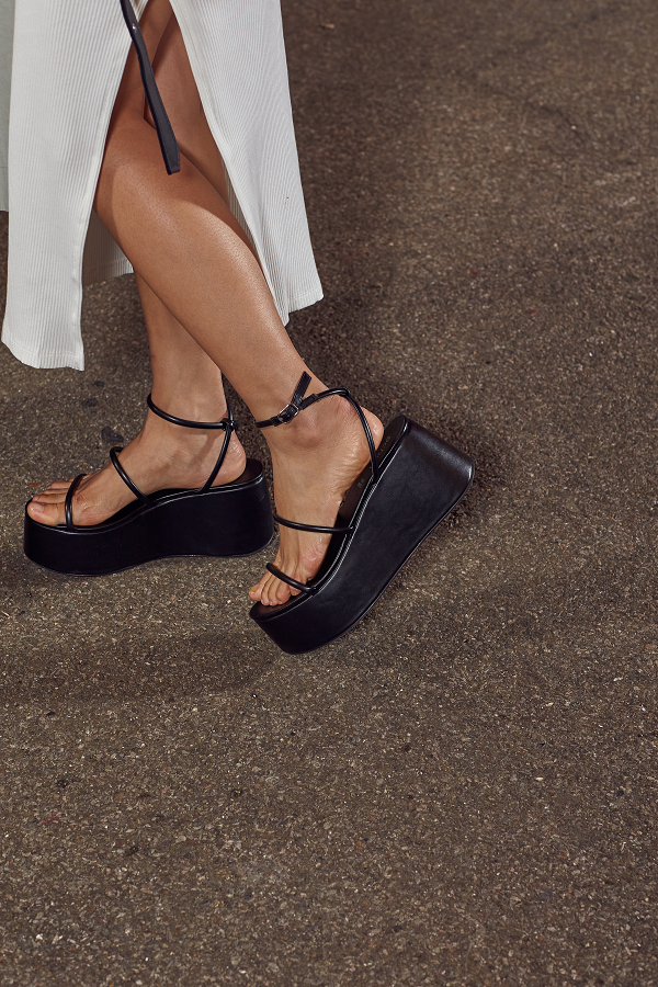 Feet wearing strappy black sandals with platforms