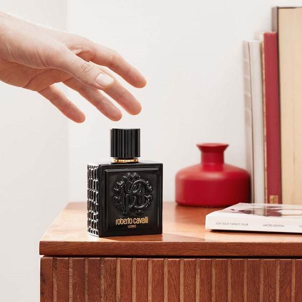 Roberto Cavelli fragrance bottle with a hand reaching for it.