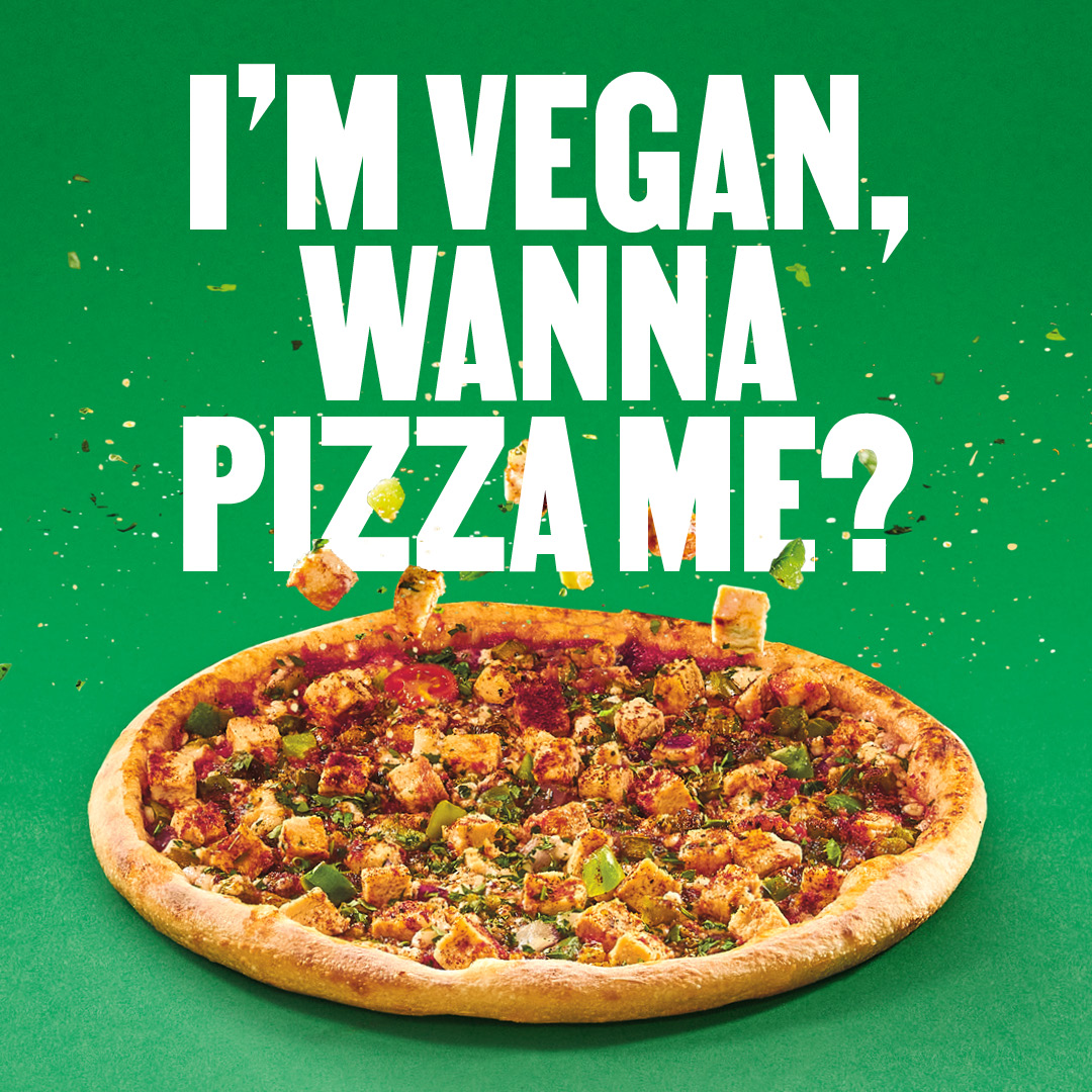 A vegan pizza with the text 'I'm Vegan, do you want a pizza me?' on top.