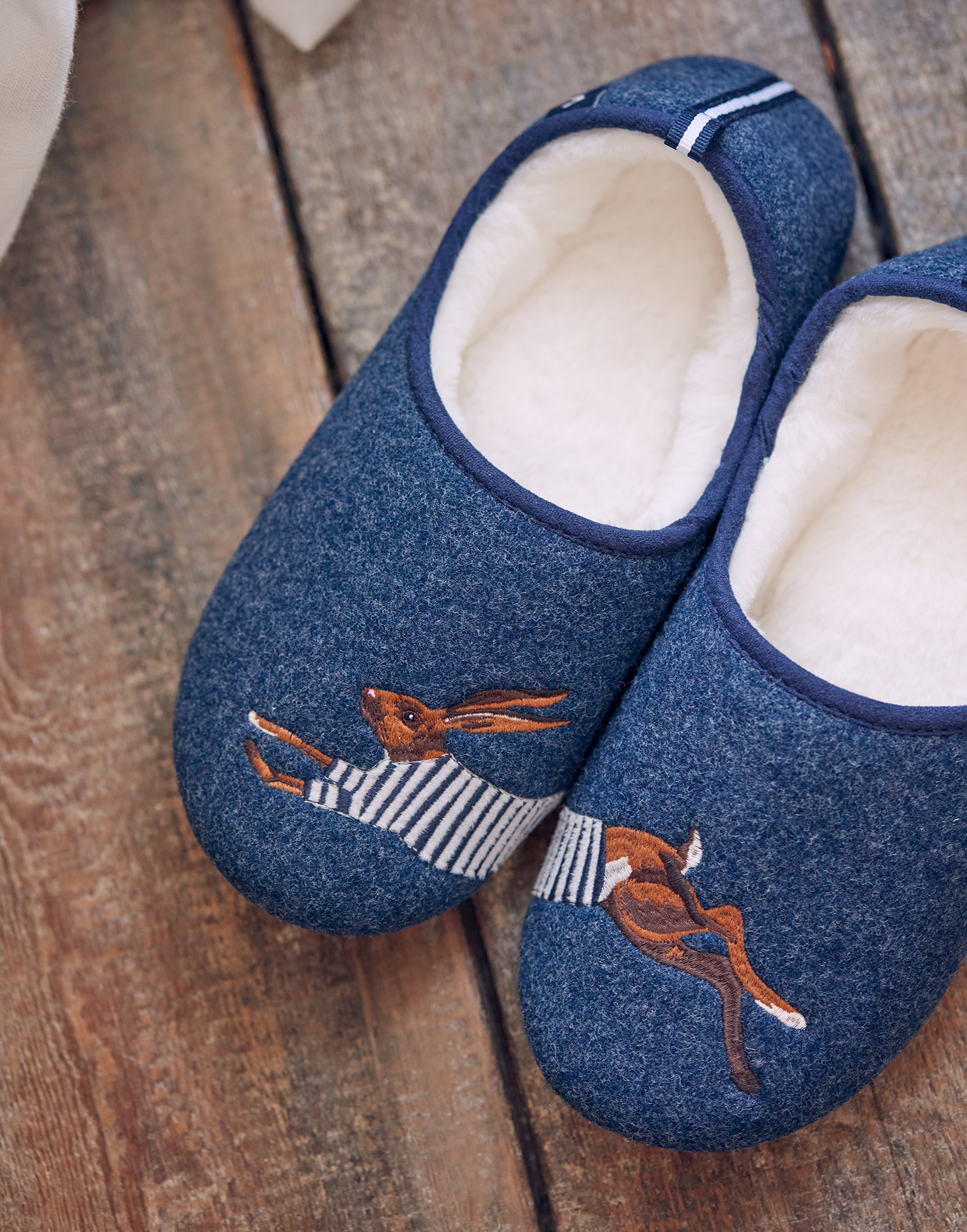 A pair of blue slippers with a hare embroidered on them.
