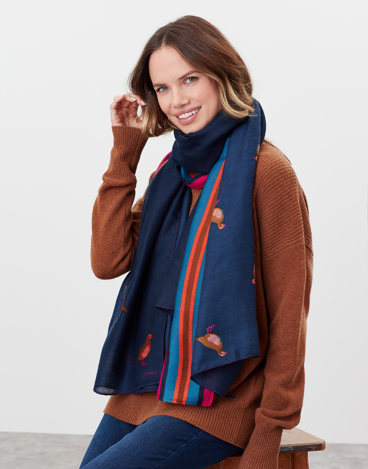 a woman wearing a rust coloured knitted jumper and blue patterned scarf.
