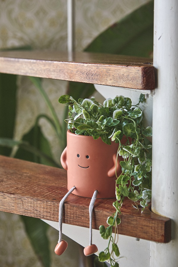 A plant pot with a smily face on the side.