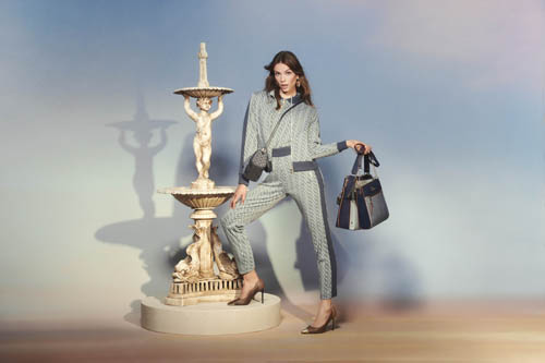 A woman wearing a grey suit and holding a handbag in front of a fountain.