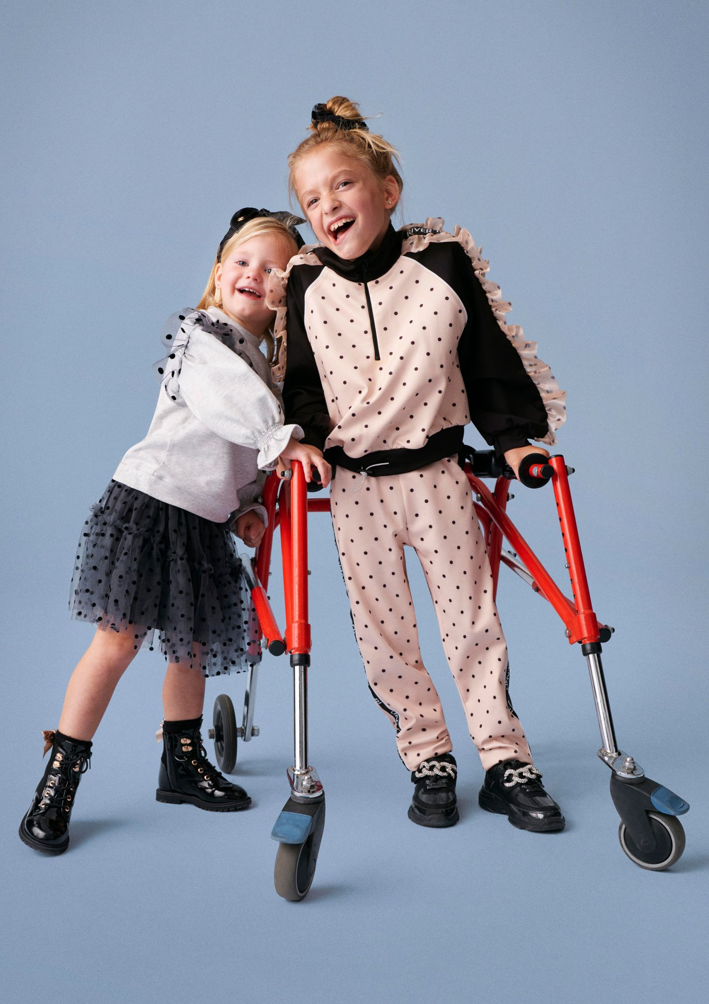 Two young girls modeling River Island's children collection for Autumn stood side by side with one girl using a walking aid