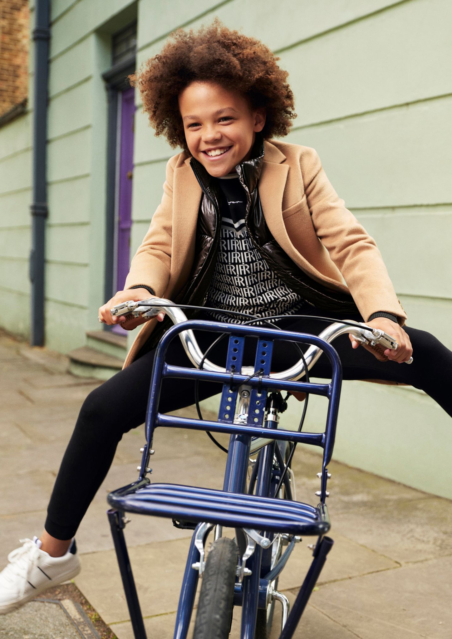 Young boy modelling River Island's autumn collection while riding a bike