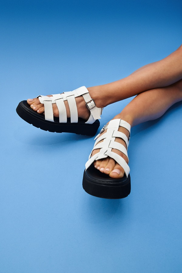 A womans feet wearing white and black flatform sandals.