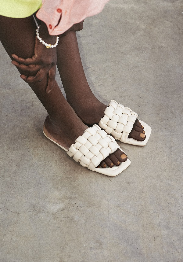 A womans feet wearing white sandals.