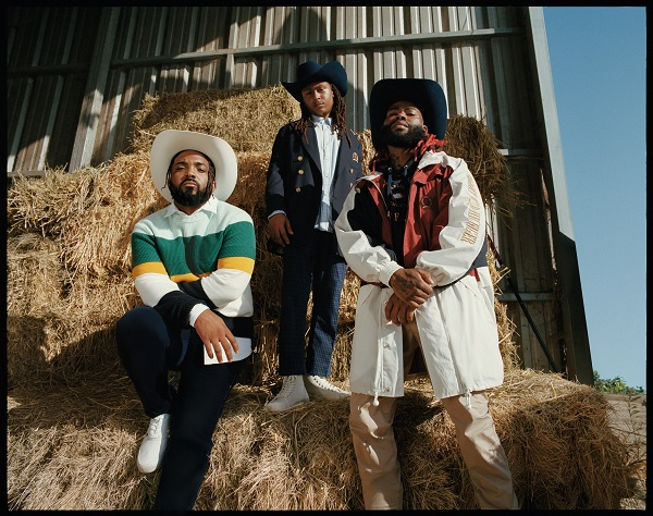 Three Men (Compton Cowboys) wearing clothes and stetson hats in a barn with haystacks.