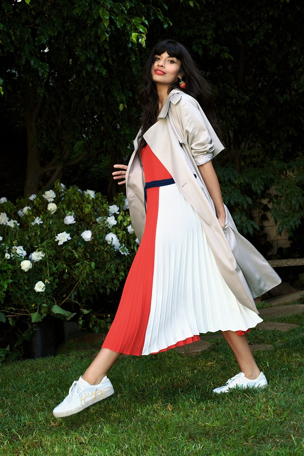 Jameela Jamil wearing a red white ad black long pleated dress and a beige macintosh style coat.