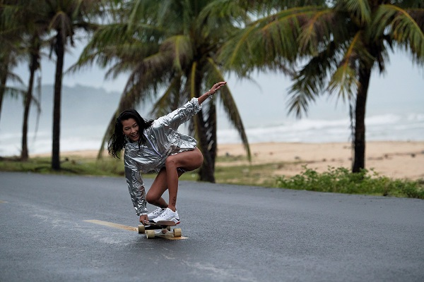 A woman (Monica) riding a skateboard down a shore front path. She is wearing a silver jacket, bikini bottoms and white trainers.